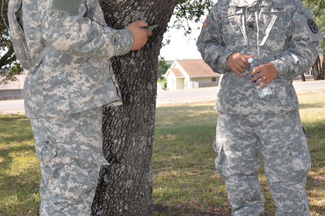 Sgt. George Soliz, CRDAMC preventive medicine NCOIC, and Spc. Ravibol Nissay, a CRDAMC preventive medicine specialist, take a break from training to rehydrate while resting under a tree. Record breaking temperatures in Central Texas have kept the Fort Hood area in heat category five throughout the month of June. (Photo by Brandy Gill, CRDAMC PAO)