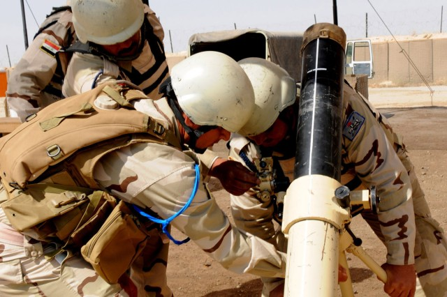 COS MAREZ, Iraq - Mortar crew members assigned to 1st Battalion, 10th Brigade, 3rd Iraqi Army Division, work to find the proper elevation and deflection on a 120mm mortar system during training at Ghuzlani Warrior Training Center, Iraq, June 13, 2011.