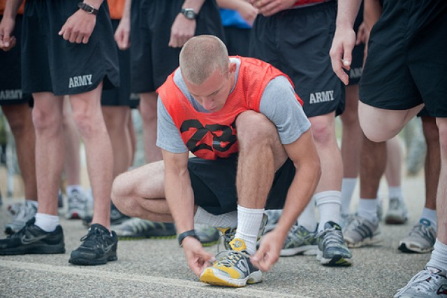 Spc. Ryan Barger, representing the 200th Military Police Command, tightens his laces prior to the start of the 2-mile run portion of the Army Physical Fitness Test at the Army Reserve Best Warrior competition at Fort McCoy, Wis. on Monday, June 20, 2011. Barger is a native of Belding, Mich.