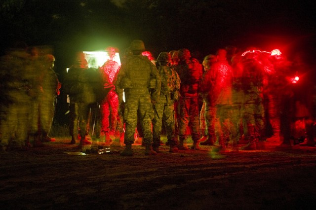Soldiers gather to recieve instructions by flashlight before participating in the Land Navigation event during the 2011 United States Army Reserve Command Best Warrior Competition at Ft. McCoy, Wis. on June 21.