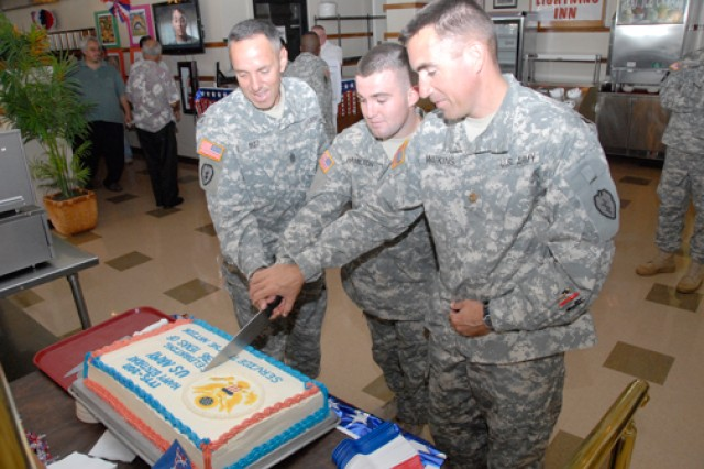 "Command Sgt. Maj. Jesus Ruiz (left), senior enlisted leader, 25th Combat Aviation Brigade, 25th Infantry Divison; Spc. Christopher Hamilton (center), Company B, 209th Avn. Support Battalion, 25th CAB; and Maj. Brian Watkins, executive officer, 209th ASB, 25th CAB, celebrate the Army's 236th birthday and cut a cake at the 25th CAB's ""Wings of Lightning"" dining facility, Wheeler Army Airfield, June 14."