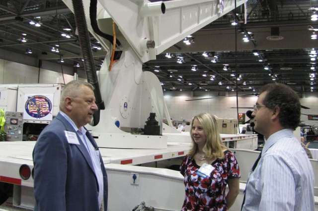 The Space and Missile Defense Command's Transportable Target Launcher makes an impressive backdrop for a conversation about launchers between Glenn Schaffer of the Targets Management Office, Program Executive Office for Simulation, Training and Instrumentation, at left, and Stephanie Long of the Space and Missile Defense Command and Joe Quinn of the Naval Surface Warfare Center in Crane, Ind. The Transportable Target Launcher was one of 135 military-related exhibits in the Von Braun Center's South Hall during Test Week 2011. The launcher is an engineering development unit that can launch target missiles ranging from 1,500 to 25,000 pounds. It is being developed for the Missile Defense Agency.