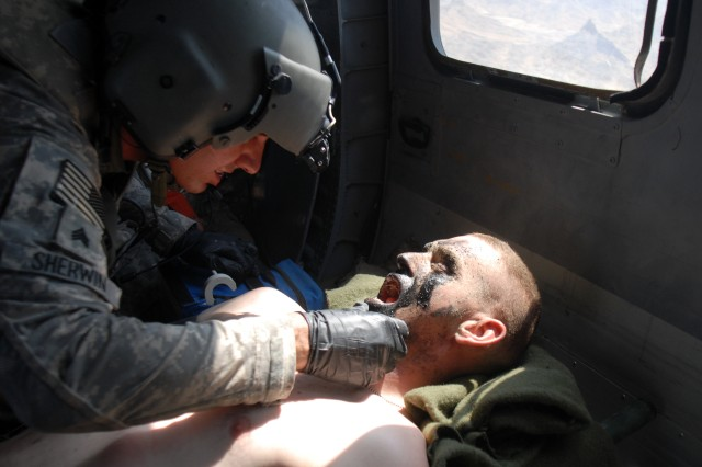 Pfc. Shawn Williams of the 1st Stryker Brigade Combat Team, 25th Infantry Division, based in Fort Wainwright, Alaska, right, is treated by flight medic Sgt. Daniel Sherwin en route to the Kandahar Airfield NATO Role 3 Multinational Medical Unit for additional treatment after he was injured by a roadside bomb, Friday, June 17, 2011, in the Kandahar province of Afghanistan. Sherwin is assigned to the Charlie Company, 1-52 Aviation Regiment, also based in Fort Wainwright.
