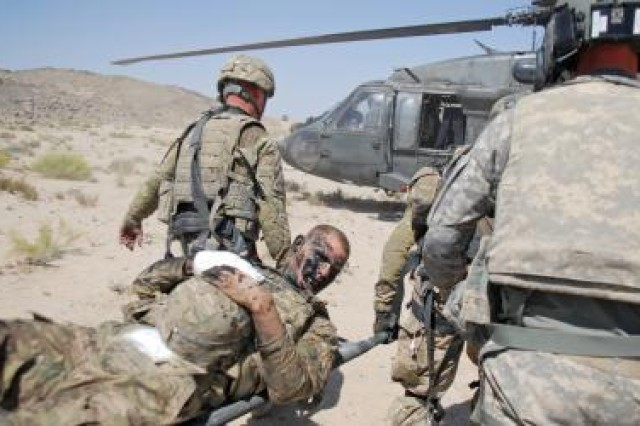 Pfc. Shawn Williams of the 1st Stryker Brigade Combat Team, 25th Infantry Division based in Fort Wainwright, Alaska, is taken to a Black Hawk helicopter for evacuation after being injured by a roadside bomb, Friday, June 17, 2011, in the Kandahar province of Afghanistan.