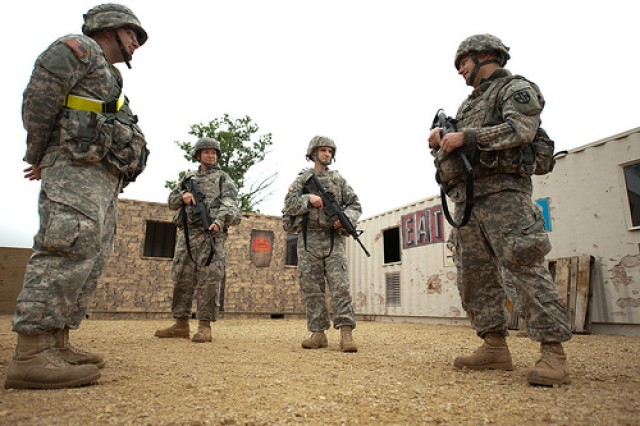 Spc. Jessica Storch, second from left, Sgt. Matthew Bledsoe, center, and Sgt. Benjamin Reehl, right, talk with Spc. Steven Ahles, 95th Training Division cadre during a break in the first Mystery Event at the Army Reserve Best Warrior competition at Fort McCoy, Wis. on Tuesday, June 21, 2011. The first mystery event included the following sub-events: evaluating and treating a casualty, reassembling a variety of small arms weapons, employing a hand-grenade at varying distances, and completing a secure communications transmission. Storch, a native of North Pole, Alaska, is representing the 9th Mission Support Command; Bledsoe, a native of Bartlett, Tenn., is representing the Military Intelligence Readiness Command; and Reehl, a native of Fort Harrison, Mont., is representing Army Reserve Medical Command.