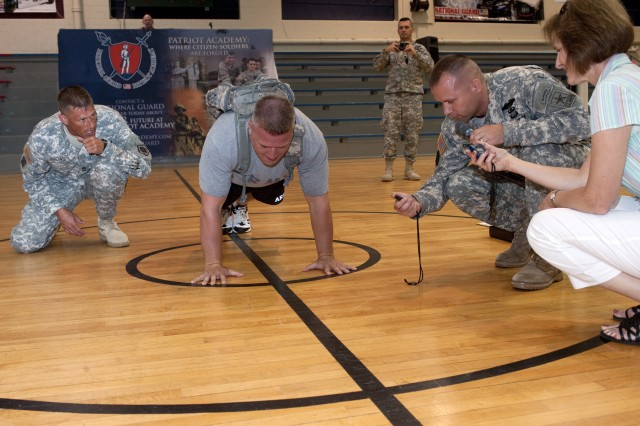 Staff Sgt. John Halsey of the Patriot Academy attempts to break a world record for the most push-ups in one minute while wearing a 40-pound pack as Sgt. First Class Jay Brown (left) cheers him on, Capt. Steven Conway (second from right) and North Vernon First Lady Joanne Campbell keep the official time, and Academy Commandant Lt. Col. William Freeman takes a photo in the background at Muscatatuck Urban Training Complex June 17, 2011. Halsey broke the record by performing 60 push-ups in 60 seconds.