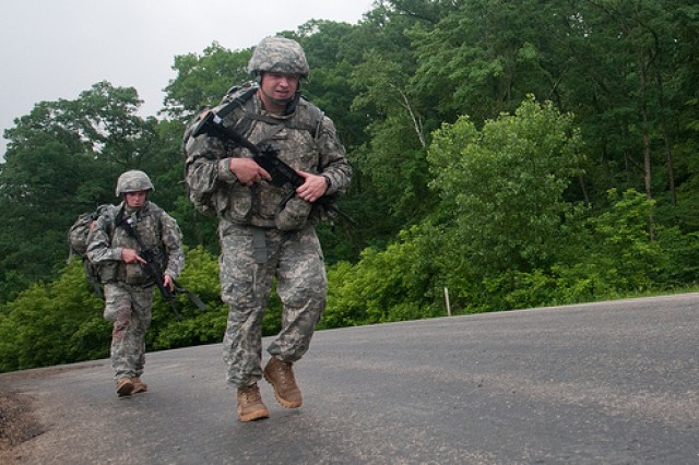 Sgt. Benjamin Reehl, front, and Spc. Kyle McLafferty, keep moving forward during the 10km road march at the Army Reserve Best Warrior competition at Fort McCoy, Wis. on Wednesday, June 22, 2011. Reehl, a native of Helena, Mont., is representing the Army Reserve Medical Command. McLafferty, a native of St. Louis, Mo., is representing the 377th Theater Support Command. The Warriors have 2 1/2 hours to complete the course carrying a full combat load along a paved course with moderate to steep road inclines.