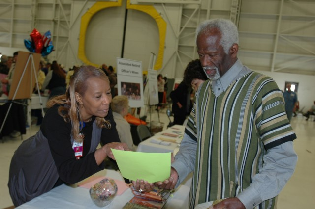 JOINT BASE LEWIS-McCHORD, Wash.,--Retired Army Maj. Mauris L. Emeka, right, receives information May 20 from Sherry G. Smith, left, a nurse in the Pediatric Clinic at Madigan. The Retiree Appreciation Day is an annual event that is now held jointly by the Army and Air Force.