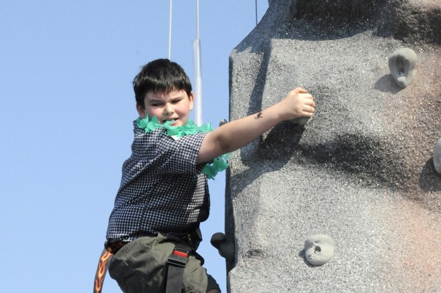 Max Black, 8, climbs the rock wall, provided by Family and Morale, Welfare and Recreation's Warrior Adventure Quest program, during Riverfest on June 19. Other FMWR activities included bull riding, face painting and inflatable play houses for children.