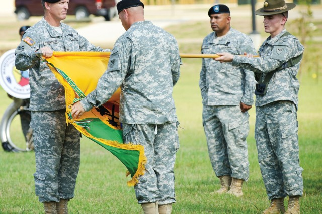 Col. Dave Thompson, left, and Command Sgt. Maj. William Beever, unfurl the 194th Armored Brigade colors during Monday's ceremony on Brave Rifles Field at Harmony Church on Fort Benning, Ga.