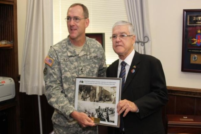 Retired Maj. Gen. Joao Henrique Carvalho de Freitas, Chief of the Doctrine Advisory Body of the Brazilian Army Education and Cultural Department, presents a plaque to Maj. Gen. Walter L. Davis, deputy director of the Army Capabilities Integration Center, during a visit to Headquarters, U.S. Army Training and Doctrine Command, at Fort Monroe Va.