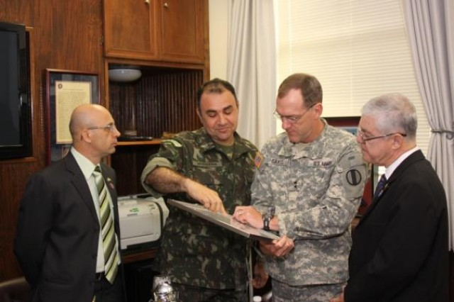 Retired Brazilian Army Col. Antonio Giacomo, of the Doctrine Advisory Body in the Brazilian Army Education & Cultural Department, looks on as the Foreign Liaison Officer for the Brazilian Army to Headquarters, U.S. Army Training and Doctrine Command, Col. Mauro Mosqueira, explains details of the presentation to Army Capabilities Integration Center deputy director Maj. Gen. Walter L. Davis and retired Maj. Gen. Joao Henrique Carvalho de Freitas of the Brazilian Army.