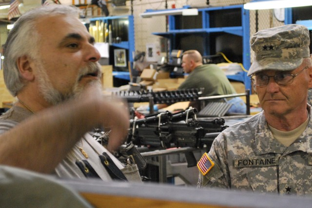 """Army Sustainment Command Commanding General Maj. Gen. Yves J. Fontaine listens as William """"Buck"""" Siconolfi, briefs him on manganese phosphate coating during the general's June 14 visit to the 404th AFSB, Joint Base Lewis-McChord, Wash."""
