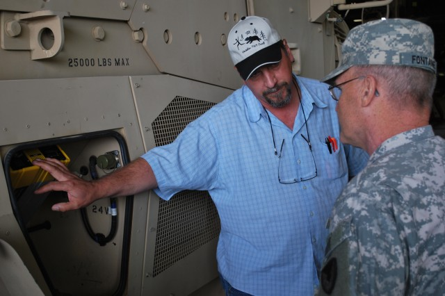 Bob Countryman describes a feature of an MRAP MaxxPro to Maj. Gen Yves J. Fontaine, Army Sustainment Command's Commanding General during the general's June 14 visit to the 404th AFSB, Joint Base Lewis-McChord, Wash.