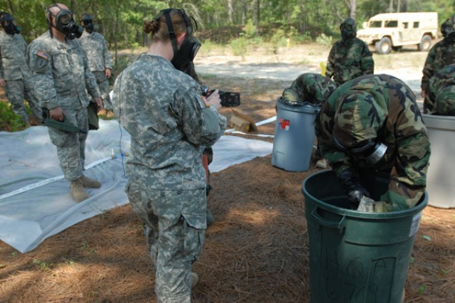 Soldiers from the 67th Signal Battalion of Fort Gordon, Ga., are timed during Exercise Red Dragon by the 327th Chemical Company of Chattanooga, Tenn., on decontamination procedures of outer garments in a steady pace during chemical decontamination simulation at Fort Gordon, Ga.
