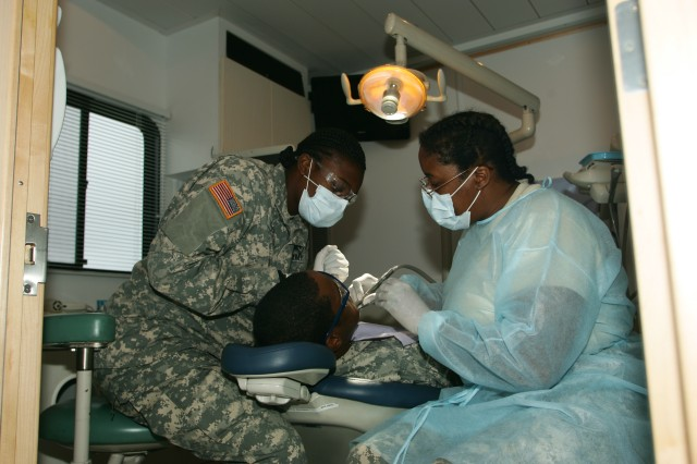 Spc. Tylethia Houston, (left) dental specialist, 350th Detachment, Charleston, S.C., and Maj. Djuana Beruk, dentist, 380th Dental Company, Memphis, Tenn., fill a tooth during Operation Ready Warrior, which provided dental services to Army Reserve Soldiers involved in Operations Diamond Saber, Essayons and Red Dragon at Fort McCoy.