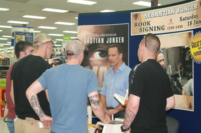 """FORT CARSON, Colo. -- Sebastian Junger, center, talks with members of 3rd Platoon, Company B, 2nd Battalion, 12th Infantry Regiment, 4th Brigade Combat Team, 4th Infantry Division, at a book signing Saturday. Junger, the author of """"War"""" and co-director of """"Restrepo,"""" met with more than 150 fans at the Fort Carson Post Exchange."""