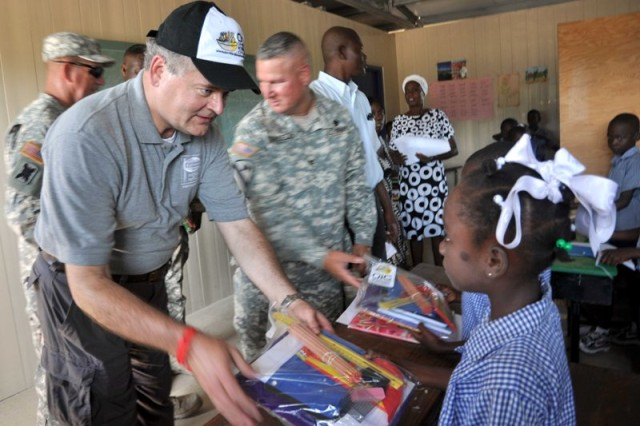 Mark Stansberry, chairman of the board of directors of People to People International, helps to distribute donated school supplies to Haitian school children here, June 16, 2011. PTPI, founded by former president, Dwight D. Eisenhower in 1956, and Operation International Children, founded by actor, Gary Sinise, and author, Laura Hillenbrand, in 2004, work with the U.S. military to assist children in countries where the U.S. military has a mission. Task Force Bon Voizen, New Horizons Haiti 2011 is a Commander, U.S. Southern Command sponsored, U.S. Army South conducted, joint foreign military interaction/humanitarian exercise under the command of the Louisiana National Guard. Task Force Bon Voizen is deploying U.S. military engineers and medical professionals to Haiti for training and to provide humanitarian services. Task Force Bon Voizen will build a school, two medical clinics and a latrine facility, as well as staff three medical clinics and one dental clinic between April 28 and June 25 in the Artibonite Department.