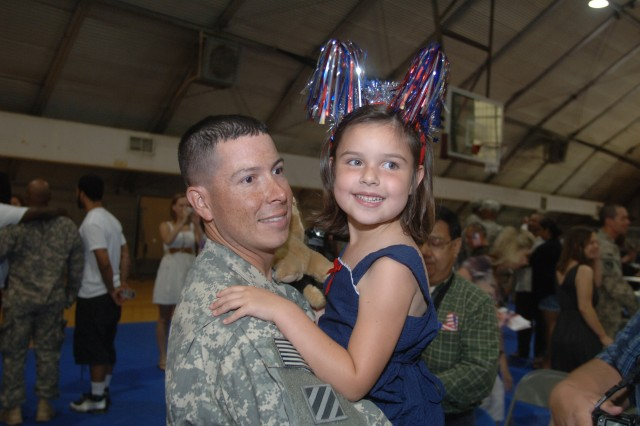Sgt. 1st Class Anthony Ovalle holds his daughter, Anaka, 4, for a photo at the 299th Engineer Company Multi-Role Bridge Welcome Home Ceremony Monday at Wells Field House.