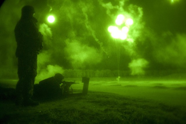 A safety looks on as Staff Sgt. Max Rees, 75th Training Division, gets a glimpse of his target as the flares lighten up the night, during the M4 night qualification on Fort McCoy, Wis. June 22, 2011. Rees is employed as a wild land firefighter for Joshua Tree National park in southeastern California.