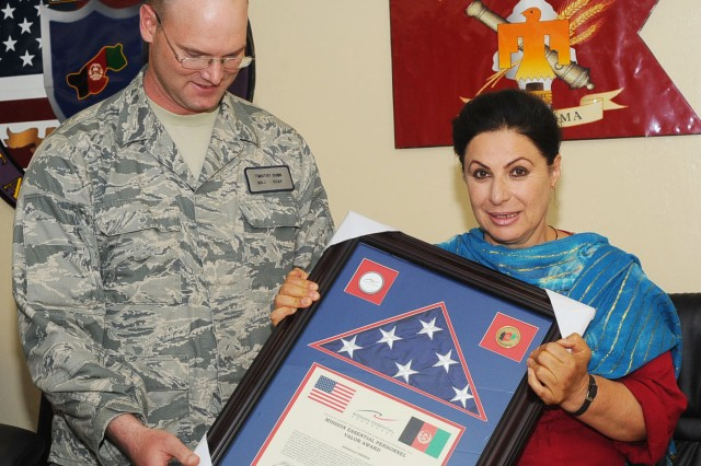 Shakilla Zikeria, an Afghan-American interpreter for Paktya Provincial Reconstruction Team, receives a valor award from Air Force Maj. Timothy Dunn, Paktya PRT Intelligence officer, at Forward Operating Base Gardez, June 17, 2011. Zikeria is the first woman in the history of U.S. efforts in Afghanistan to receive the Military Essential Personnel Award for Valor.