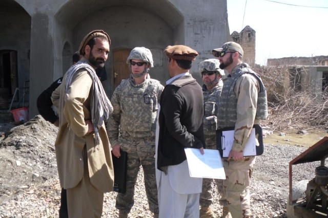 Air Force Staff Sgt. Kyle Capps (center), Army Maj. David Troutman, construction chief (right), and Brandon Mc Alexander, contracting officer representative, speak with the local Afghanis about a contracting project to help rebuild the local area. All three are team members of the Salerno, Afghanistan Regional Contracting Center.