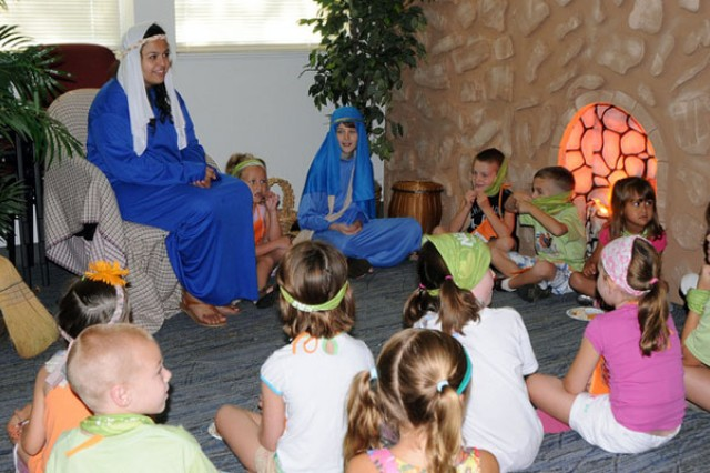 Nicole Fenner and Wyatt Collard, dressed in blue robes, assume the roles of Mary and Jesus to give Vacation Bible School attendees a depiction of Jesus' first trip to Jerusalem as an adult man to observe Passover.