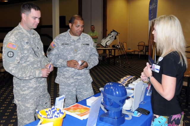 Capt. Dave Winter and Maj. Jesse Delgado, B Co., 1st Bn., 212th Avn. Regt., get information about sleep disorders from Dana Florea, Southeast Alabama Medical Center account executive, at the first-ever Men's Sports, Fitness and Wellness Expo at The Landing June 15.