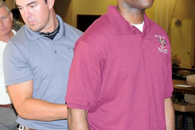 Nick Love, Hollowell Chiropractic wellness trainer, checks the spine of Spc. Jerald Barley, USAAMC optometry technician.