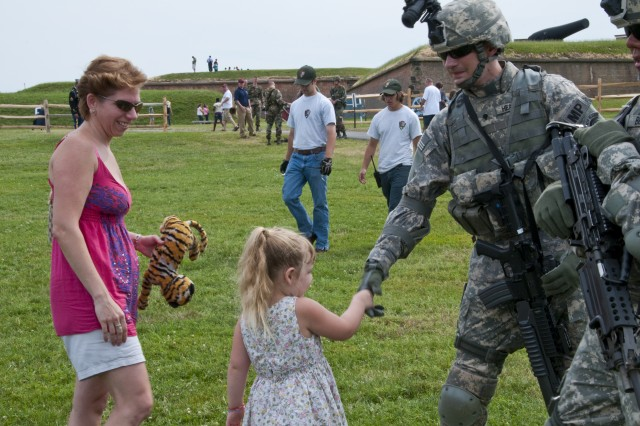 Olivia Allen, 5, of Baltimore, shakes hands with Spc. Dustin Heacock, 289th Military Police Company, after the Army's Twilight Tattoo ceremony at Fort McHenry National Monument and Historic Shrine. Heacock performed tactical maneuvers with his unit during Friday's ceremony. Fort Meade will mark the adoption of the Declaration of Independence on July 4 with the annual Independence Day commemoration, which will begin on McGlachlin Parade Field at noon.