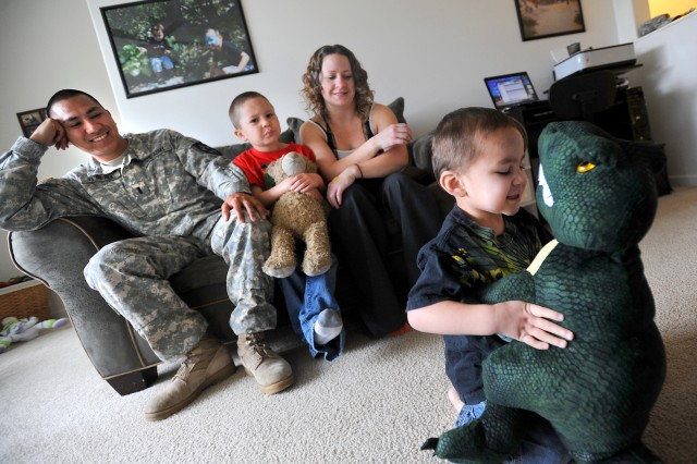 Tonio Terlaje, 3, right, plays with his pet dinosaur as his father 1st Lt. Antonio Terlaje, older brother, Xavier, 5, and mother, Rose, look on June 14 at their JBLM home. Tonio was diagnosed with autism when he was 22 months old.