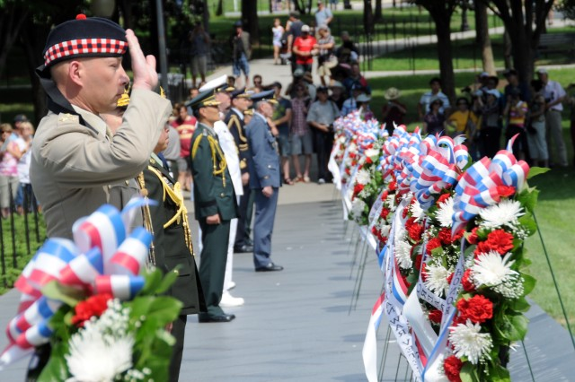 A military officer of the United Kingdom salutes, after having laid a wreath at the  Korean War Veterans Memorial in Washington, D.C., June 24.