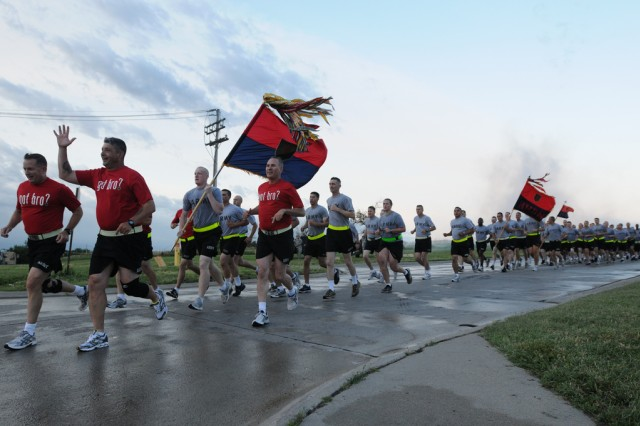 Maj. Gen. William Mayville, commanding general of the 1st Inf. Div. and Fort Riley, Kan., far left, and Division Command Sgt. Maj. Jim Champagne, right, lead a four-mile division run, June 27, 2011, on Custer Hill.