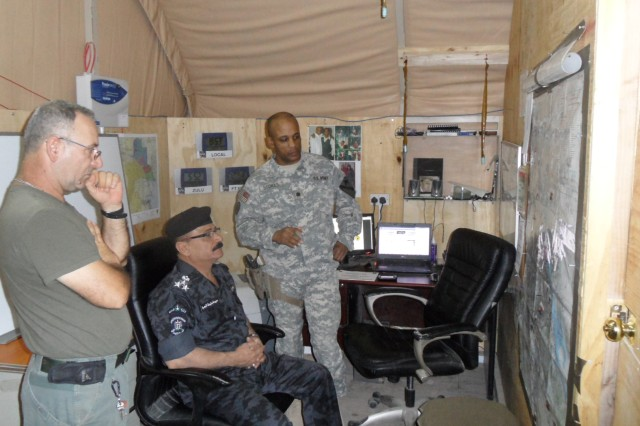BASRAH, Iraq – Lt. Col. Gregory Stokes, commander of STT Enforcer, Advise, Train and Assist, 1-12 Cav., 1st Cav. Div., briefs the Provincial Chief of Police Brig. Gen. Faisal on LOEs on June 9, 2011.