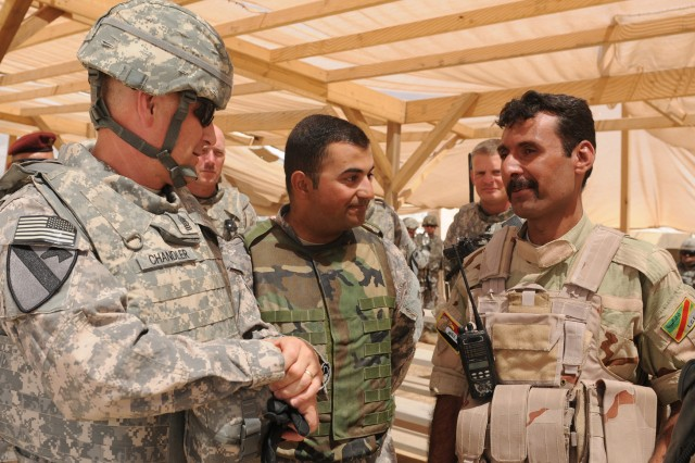 COS MAREZ, Iraq - Sgt. Maj. of the Army Raymond F. Chandler III speaks with Sgt. Maj. Bolan, senior enlisted leader, 1st Bn, 10th Bde, 3rd Iraqi Army Div., about the combat readiness of Iraqi soldiers at the GWTC, near Mosul, Iraq, June 23, 2011.