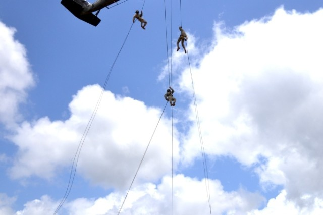 """Soldiers from the Mobile Training Team Air Assault Course rappel out of a UH-60 Black Hawk helicopter from 2nd Assault Helicopter Battalion, 25th Aviation Regiment, """"Diamond Head,"""" 25th Combat Aviation Brigade, on the East Range Complex near Wheeler Army Airfield, Hawaii, May 24, 2011."""