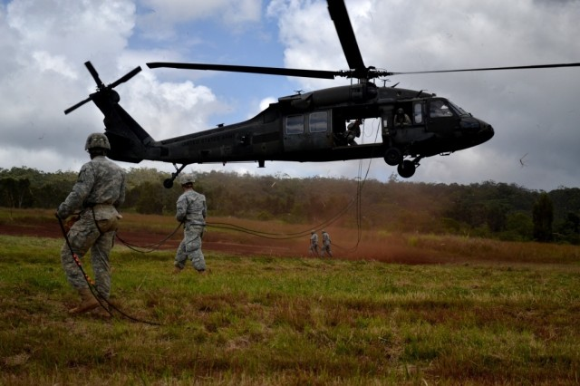 """Soldiers in the Mobile Training Team Air Assault Course guide the rappel ropes from a UH-60 Black Hawk helicopter from 2nd Assault Helicopter Battalion, 25th Aviation Regiment, """"Diamond Head,"""" 25th Combat Aviation Brigade, on the East Range Complex near Wheeler Army Airfield, Hawaii, May 24, 2011."""