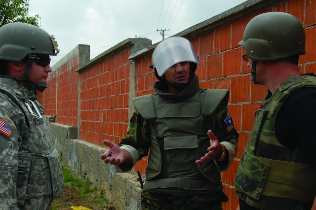 Sgt. Stephen Rodgers, left, and Kosovo security forces explosive ordnance disposal specialist OR-6 Mustaf Kryeziu, center, determine the scene safe and discuss the best method for transporting and disposal of two small boxes of bulk explosives found in the backyard of a local resident of Tica, Kosovo. The Kosovo security forces and KFOR explosive ordnance disposal teams work in conjunction to identify and properly dispose of found ordnance.