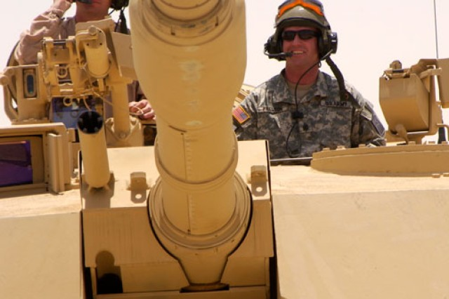 Then-Sgt. Maj. of the Army Kenneth O. Preston (right), and Sgt. 1st Class Dale Green, Army Field Support Battalion, Kuwait, prepare to drive an M1A1 tank at Camp Arifjan, May 27, 2006.