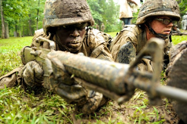A muddied cadet takes aim at a mock target during an individual tactical training exercise at the 2010 Leader's Training Course on Fort Knox, Ky.