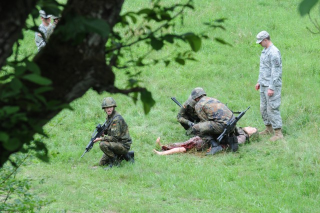 German Soldiers of the 950th Psyops Battalion treat a simulated casualty during Tactical Combat Casualty Care (TC3) training June 16, as instructor Spc. Paul Evans, a combat medic from the 557th Medical Company (Area Support) looks on. (US Army photo by Sgt. 1st Class Christopher Fincham)