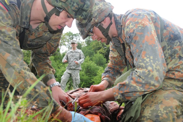 German Soldiers of the 950th Psyops Battalion treat a simulated casualty during Tactical Combat Casualty Care (TC3) training June 16, as instructor Sgt. Kevin Perry, a combat medic from the 557th Medical Company (Area Support) looks on. (US Army photo by Sgt. 1st Class Christopher Fincham)