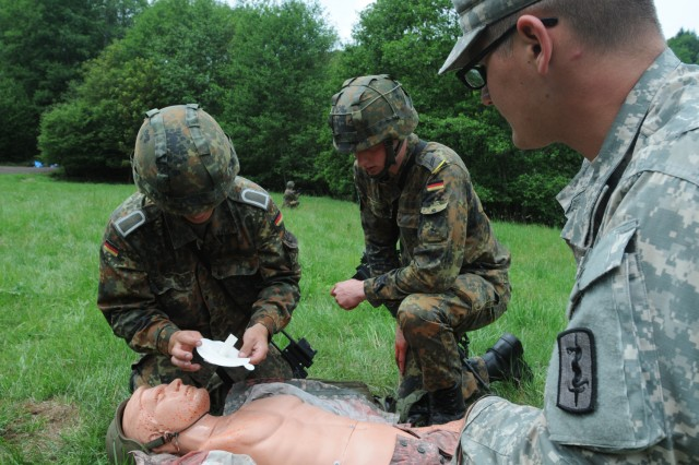 German Soldiers of the 950th Psyops Battalion treat a simulated casualty during Tactical Combat Casualty Care (TC3) training June 16, as instructor Spc. Charles Auterberry, a combat medic from the 557th Medical Company (Area Support) looks on. (US Army photo by Sgt. 1st Class Christopher Fincham)