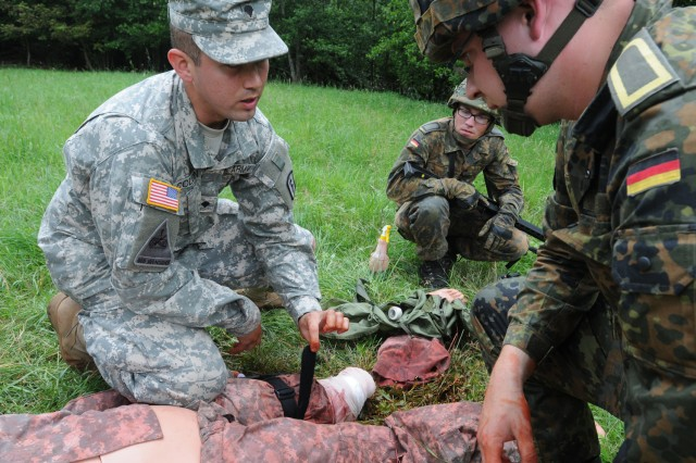 Spc. Abimael Colon, a combat medic from the 557th Medical Company (Area Support) demonstrates how to apply a tourniquet to Soldiers of the German Army's 950th Psyops Battalion during Tactical Combat Casualty Care (TC3) training June 16, in Baumholder, Germany. (US Army photo by Sgt. 1st Class Christopher Fincham)