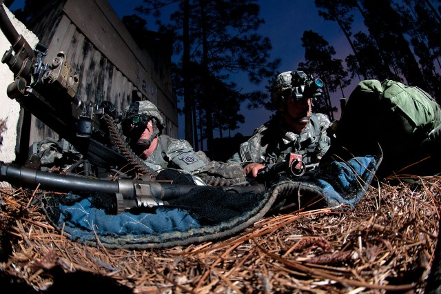Two paratroopers with the 82nd Airborne Division's 1st Brigade Combat Team pull security at a mock village during a joint operational access exercise, June 27, 2011, at Fort Bragg, N.C.  The Soldier at left is armed with an M240-B machine gun.