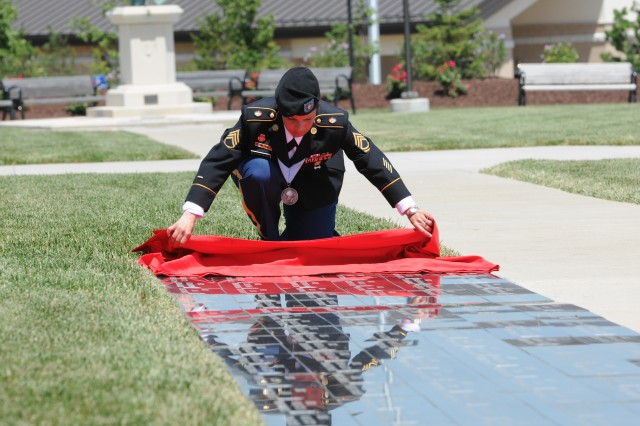 Sgt. 1st Class Maria Estremera pulls back a red sheet to reveal the names of 11 fallen 1st Infantry Division Soldiers June 29, 2011, during a ceremony at Victory Park on Fort Riley, Kan. In total, 22 Soldiers who died while serving with the division in Iraq or Afghanistan during the past 18 months were honored during the ceremony.