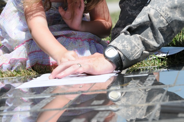 Hannah Maher makes a rubbing of the memorial stone honoring her father, Sgt. Brent Maher, following the Victory Park Ceremony, June 29, 2011, at Fort Riley, Kan. Sgt. Maher was one of 22 Soldiers who died while serving with the division in Iraq or Afghanistan during the past 18 months, who were honored during the ceremony.