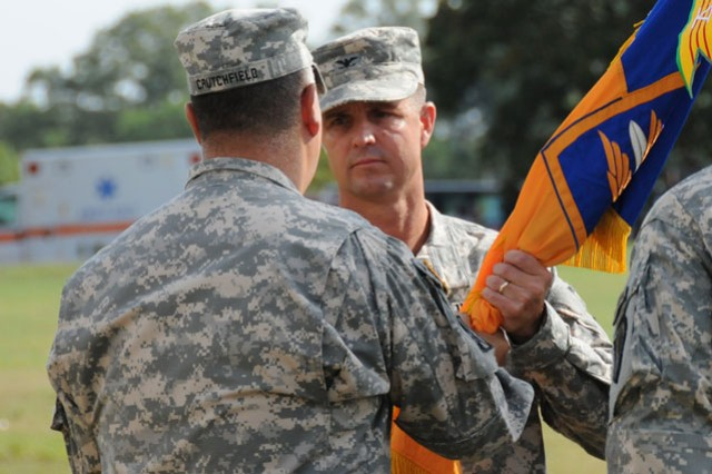 Col. Brian D. Bennett, 1st Avn. Bde. commander, takes the brigade colors from Maj. Gen. Anthony G. Crutchfield, USAACE and Fort Rucker commanding general, during a change of command ceremony at Howze Field June 24.