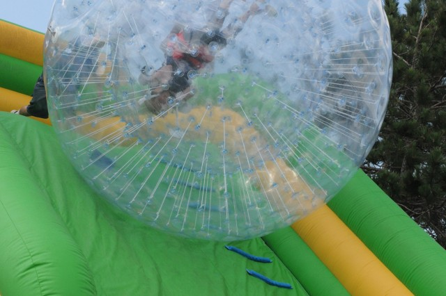 Amy Gill, whose husband is currently deployed with Headquarters and Headquarters Battalion, 10th Mountain Division (LI), rolls down an inflatable slide in a giant bubble at Mountainfest on June 23.
