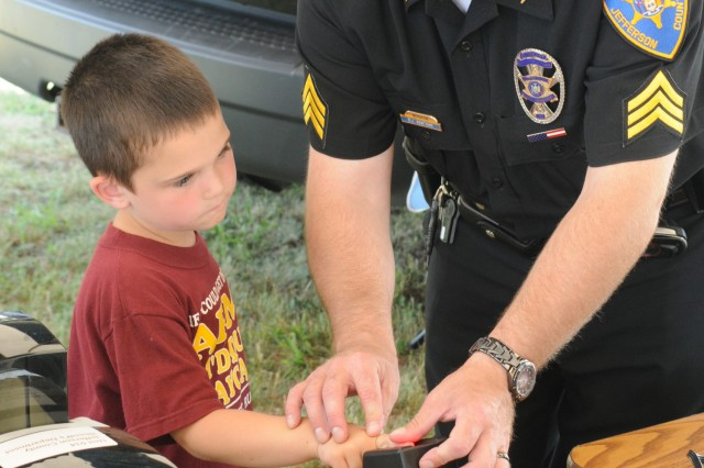 Sgt. Rob Newtown, Jefferson County Sheriff's Department, takes 6-year-old Jeremiah Heinrichs' fingerprints for an identification card.